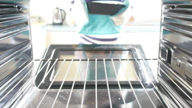 donna mettendo in forno per il pane di cottura - pane forno video stock e b–roll