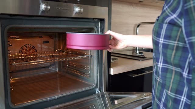Woman putting cake in the oven and setting the oven temperature