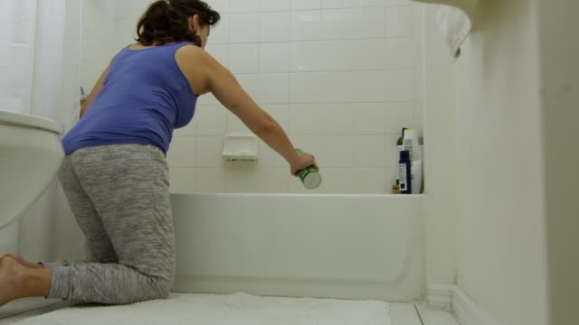 Woman putting cleaning product on bathtub during quarantine video