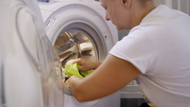 Woman putting clothes into the washing machine