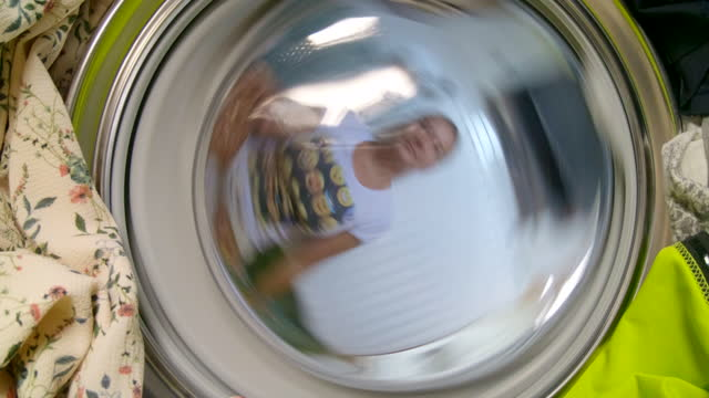 Woman putting dirty clothes into the washing machine