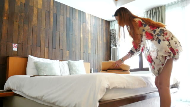 Woman putting fresh towels on the bed