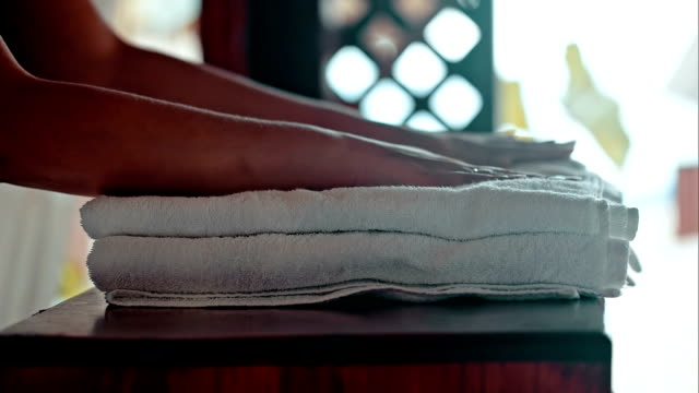 woman putting fresh towels on the table and flower on it - spa stock videos & royalty-free footage