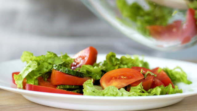 Woman putting fresh vegetable salad from bowl to plate, healthy appetizer, detox video