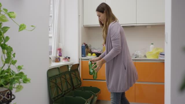 vídeos de stock e filmes b-roll de woman putting glass bottles into recycle bins - economia circular