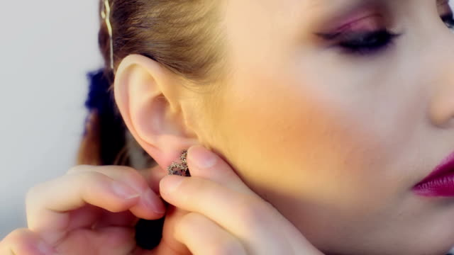 Woman putting her earrings video