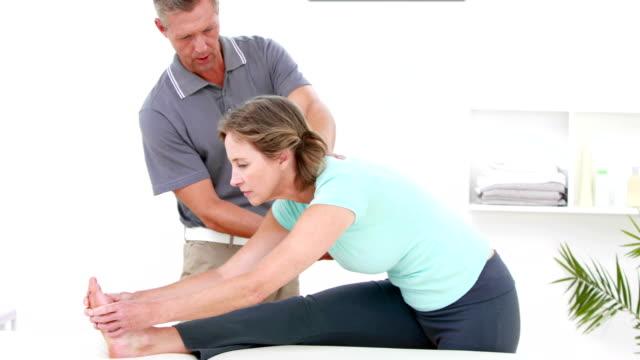 donna mettendo i suoi piedi su un tavolo mentre si estende la gamba - mani sui fianchi video stock e b–roll