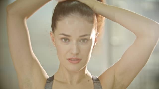 stockvideo's en b-roll-footage met een vrouw zetten haar haar in paardenstaart - paardenstaart haar naar achteren