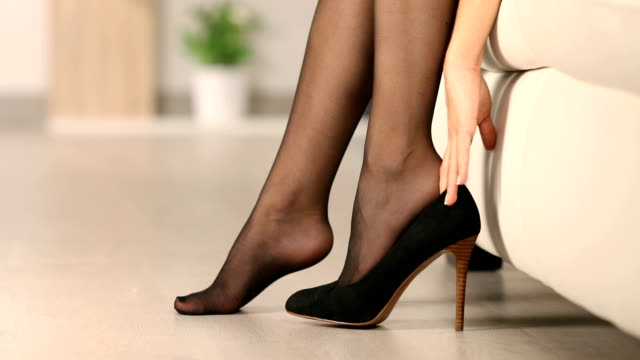 Woman putting high heel shoes and walks at home