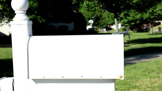 donna mettendo mail nella cassetta postale e segnalazione di bandiera - inviare video stock e b–roll