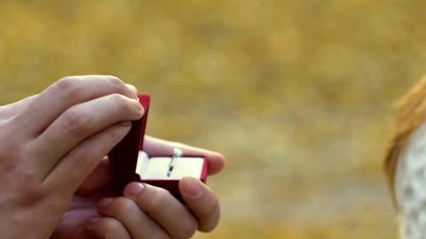 donna che mette su anello di diamanti al dito nel parco, gioielli costosi di lusso - fidanzato video stock e b–roll