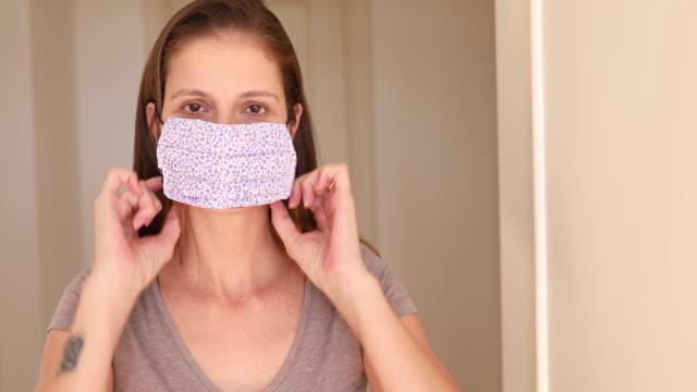 frau setzt auf hausgemachte schutzmaske - selbstgemacht stock-videos und b-roll-filmmaterial