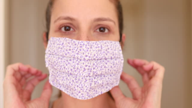 vídeos de stock e filmes b-roll de woman putting on homemade protective mask - têxtil