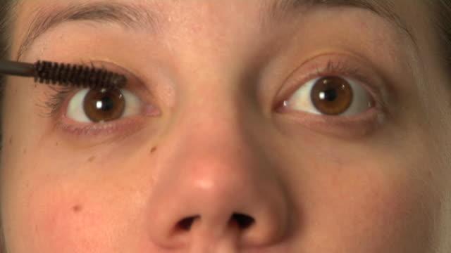 Woman putting on mascara video