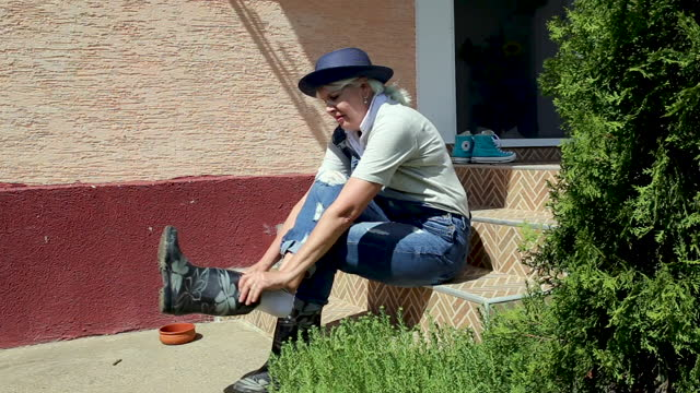 Woman putting on rubber boots, starting working garden, planting seedlings