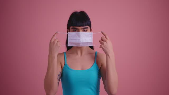 vídeos de stock e filmes b-roll de woman putting on surgical mask for virus prevention - covid hair