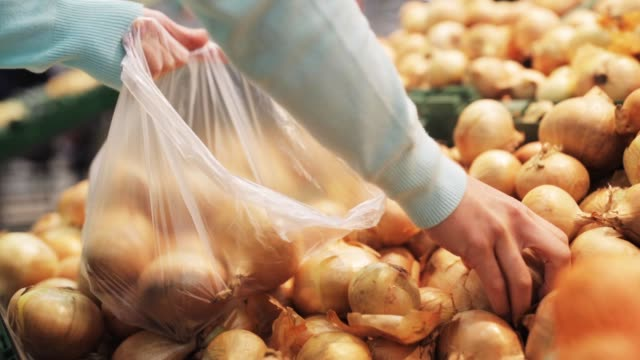 woman putting onion to bag at grocery store shopping, sale, food, consumerism and people concept - woman putting onion to plastic bag at grocery store onion stock videos & royalty-free footage