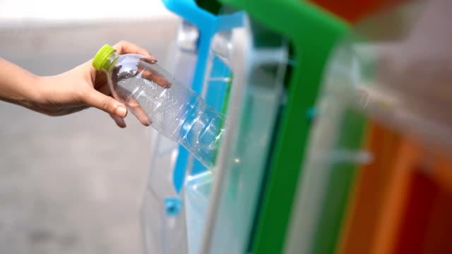 slo mo woman putting plastic bottles in recycle bin garbage - odzyskiwanie i przetwarzanie surowców wtórnych filmów i materiałów b-roll