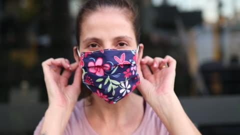 vídeos de stock e filmes b-roll de woman putting protective mask on close up - feito em casa