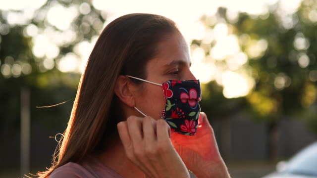 Woman putting protective mask on profile view