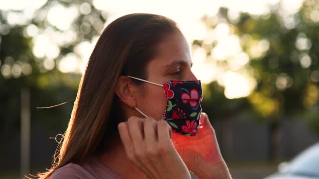 woman putting protective mask on profile view - nakładać filmów i materiałów b-roll