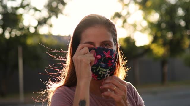 woman putting protective mask on - nakładać filmów i materiałów b-roll