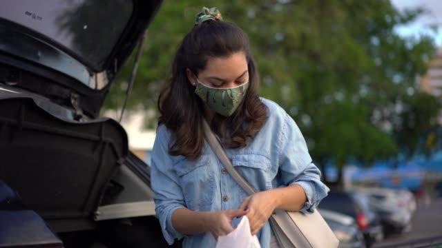 vídeos de stock, filmes e b-roll de mulher colocando compras no tronco durante a pandemia coronavírus - brasileiro pardo