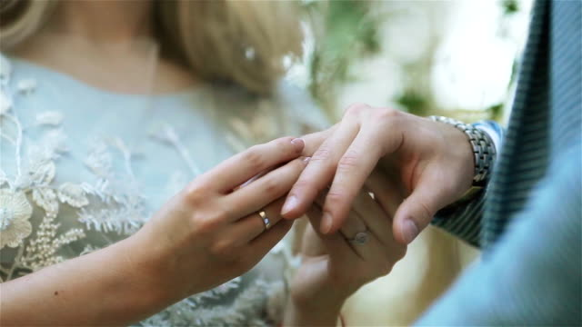 woman putting ring on mans finger close up through veil or sun light. girlfriend proposing to girlfriend as gender equality concept. exchanging wedding rings at ceremony in nature outdoors - mano donna dita unite video stock e b–roll