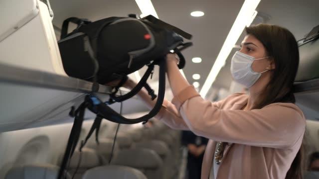 frau legt koffer in den offenen baumstamm der flugzeugkabine tragen gesichtsmaske - travel stock-videos und b-roll-filmmaterial