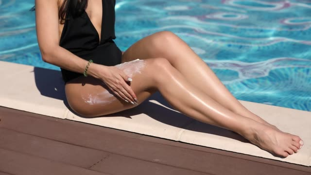 Woman putting sunscreen spf cream on her leg, skincare protection video