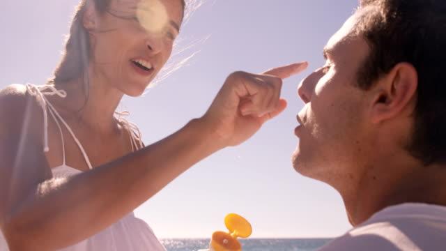 woman putting sunscreen to her boyfriend - sun cream stock videos & royalty-free footage