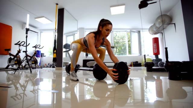 vidéos et rushes de femme mettant des poids sur le barbell - mince
