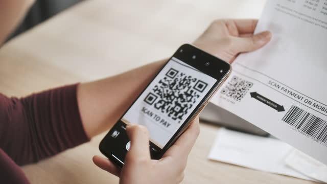 携帯電話でビルに支払う女性qrコード - クレジット決済点の映像素材/bロール