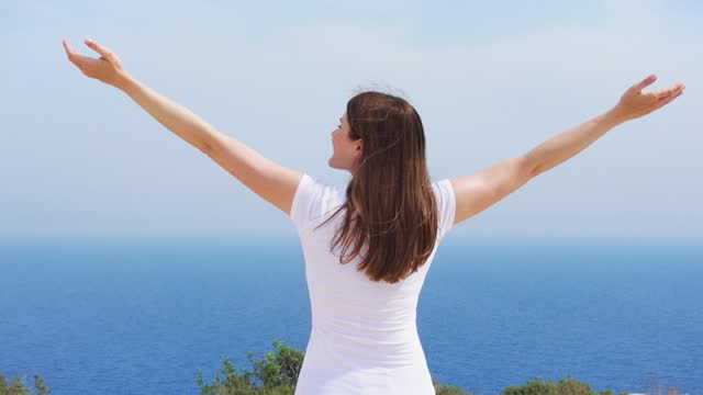 Woman raise arms up at cliff against blue sea. Female traveleer outstretching hands in slow motion