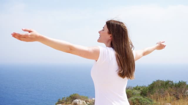 woman raise arms up at cliff against blue sea. female traveleer outstretching hands in slow motion - maglietta video stock e b–roll
