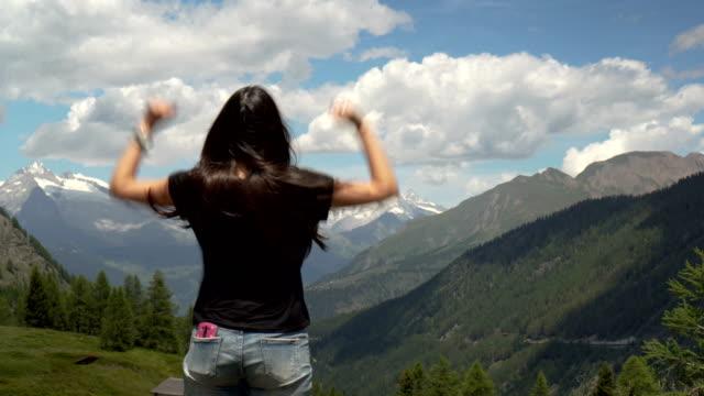 woman reaching the mountain top on the alps - ekoturystyka filmów i materiałów b-roll