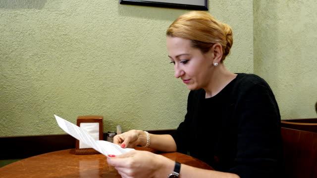 Woman read paper letter at cafe, side portrait shot video