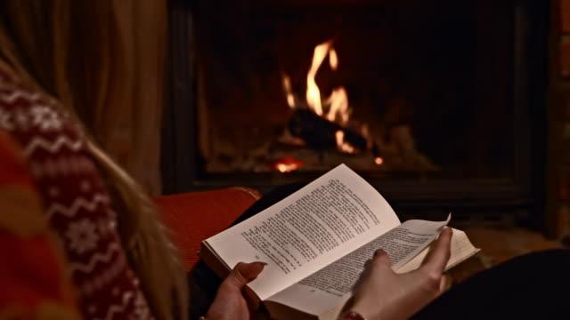 vídeos de stock e filmes b-roll de ds mulher um ler um livro pela lareira - aconchegante