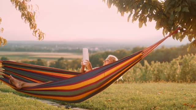 ds woman reading a book in a hammock in the vineyard - amaca video stock e b–roll