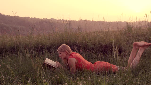 Woman reading a book lying on the grass. video