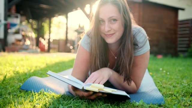 Woman Reading A Book Outdoors And Looking At Camera video