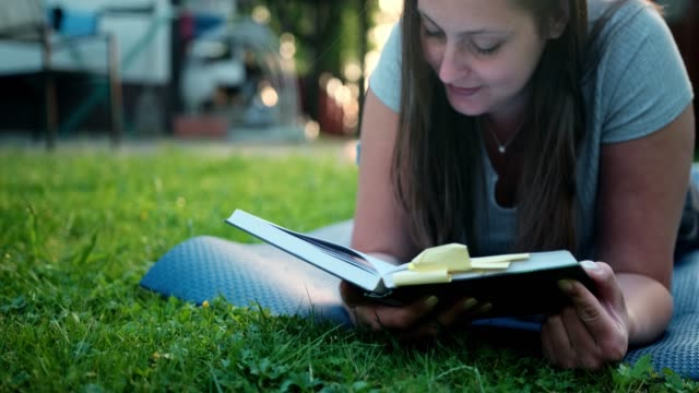 Woman Reading A Book Outdoors And Lying In The Grass video