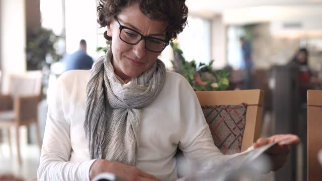 vidéos et rushes de femme lisant un magazine dans un restaurant - 40 44 ans