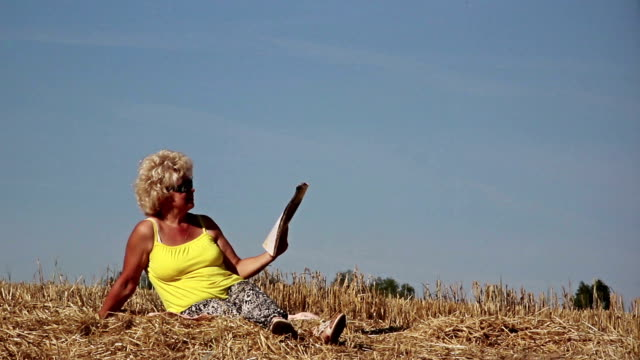 woman reading a magazine on the field, a woman in a yellow T-shirt sunny weather video