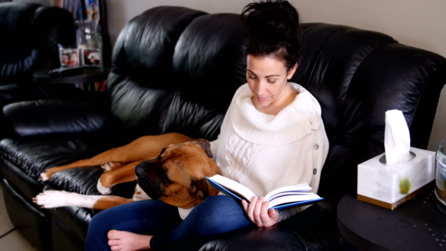 Woman reading a novel while dog relaxing on her lap video