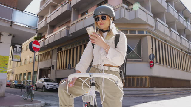 Woman reading a text while on the go cycling to the office video