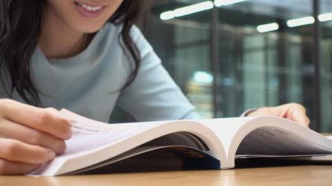lettura donna e pagina open book - imparare video stock e b–roll