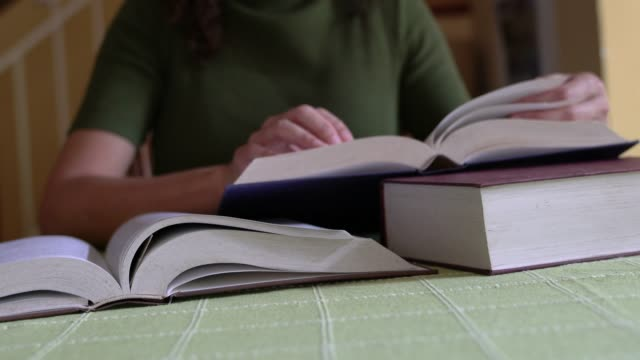 vídeos y material grabado en eventos de stock de mujer leyendo y estudiando, pasando páginas y bajando sus gafas de lectura. - pegajoso