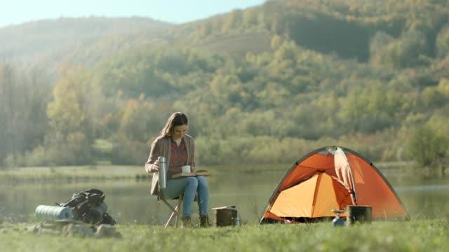 本を読んでいて、湖のほとりにコーヒーの女性 ビデオ