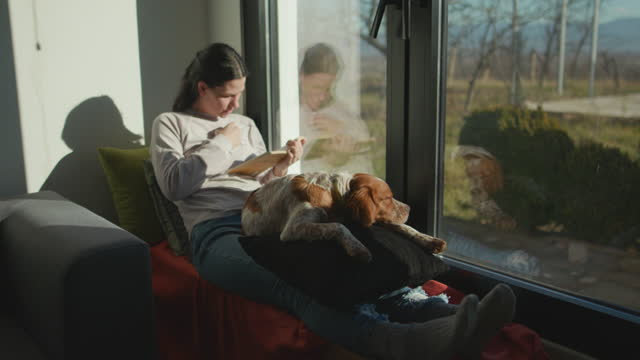 Woman reading book at home with a dog in her lap